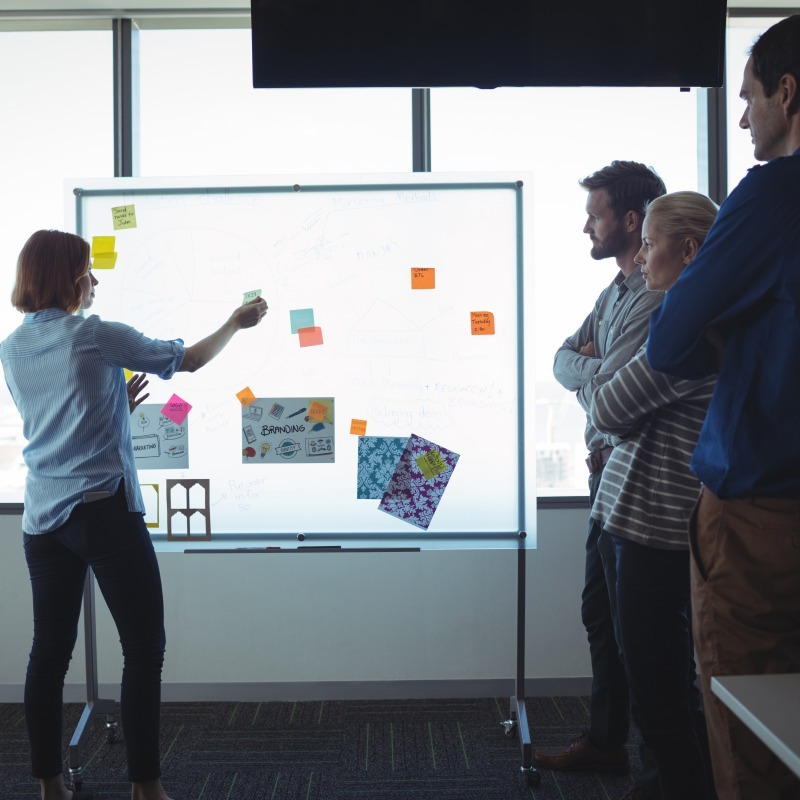A financial adviser pay per click campaign designer standing at a white board creating a concept for a social media campaign observed by three colleagues